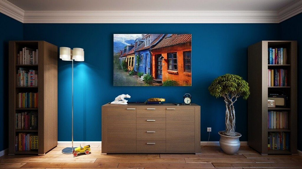 blue wall with picture of houses, dresser, lamp and plant - look for smile